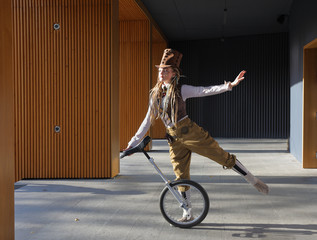 Young lady in a fantasy clothes with unicycle
