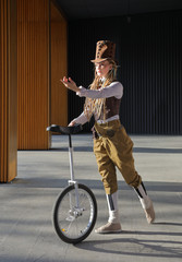 Pretty young woman in a fantasy clothes with unicycle