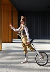 Young woman in a fantasy clothes with unicycle