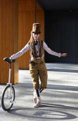 Pretty girl in a fantasy clothes and make-up with unicycle