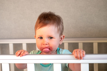 Cute baby standing in a white wooden bed. Little girl learning to stand in her crib.