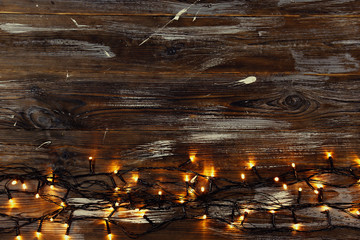 Christmas background concept. New year decoration lights, garland with many small lamps of differentcolor shine on brown grunged wooden table. Top view, flat lay, copy space.