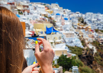Tourist girl taking picture with smartphone in beautiful Santorini