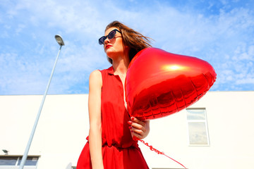 Female model with red heart ballon outside on a sunny day