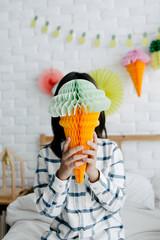 Boy holding big ice-cream cone shaped paper honey comb ball