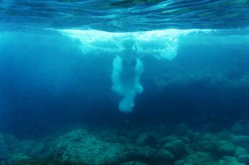 Woman jumping in ocean