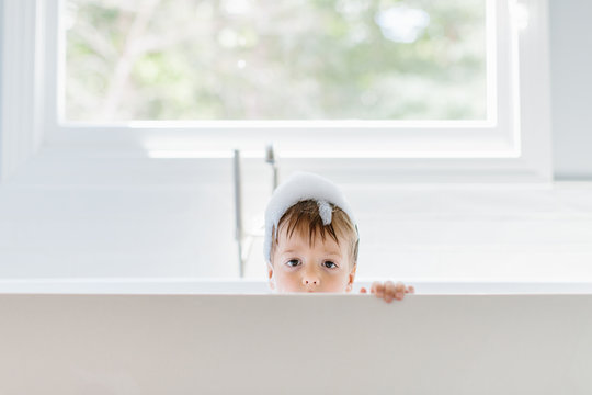 Cute young boy with suds on his head peeking up from a bathtub