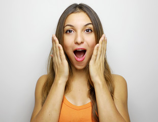 Woman happy and surprised shouts holds cheeks by hand. Beautiful girl with orange tank top excited on white background.  Expressive facial casual woman.