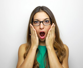 Image of surprised woman wearing glasses and dressed in green drees over white background. Look at camera.
