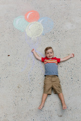 Cute young boy laying on the ground while holding on to balloons drawn in chalk