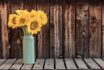 A bunch of sunflowers in a green bucket on a rustic plank table.