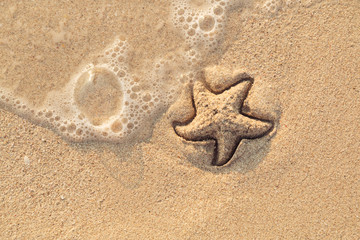 Starfish drawn on the beach sand being washed away by a wave. Foaming sea wave coming to wash a picture on wet yellow beach sand. Holiday and vocation message. View from above. Copy space.