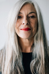 Portrait of an attractive senior woman with grey long hair looking at camera.