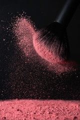 Make-up brush with pink face powder against dark background