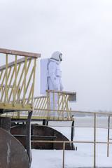Unrecognizable cosmonaut on snowy lakeside