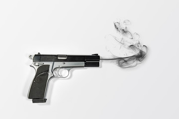 A semi-automatic 9mm smoking hand gun over bright white background with plenty of negative space for copy.
