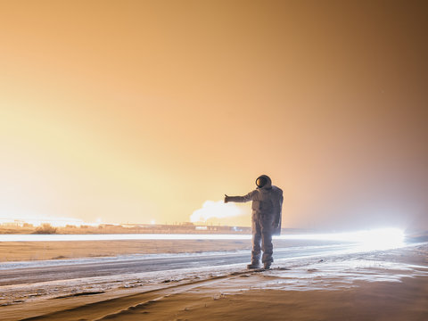 Astronaut hitchhiking in winter
