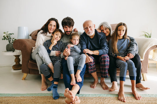 Portrait of family wearing pajama sitting on a sofa.