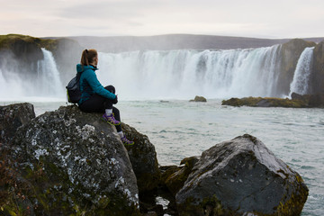 Hiker looking at splashing Godafoss waterfall, Iceland
