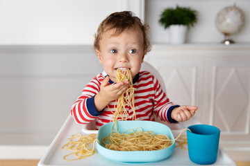 Funny baby eating a mouthful of spaghetti noodles