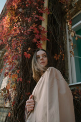 portrait of stylish girl in coat near the old building with red leaves