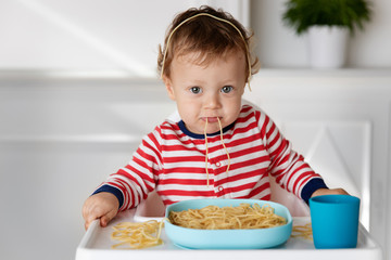 Baby making funny face while eating spaghetti noodles