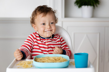 Funny toddler eating a mouthful of spaghetti noodles