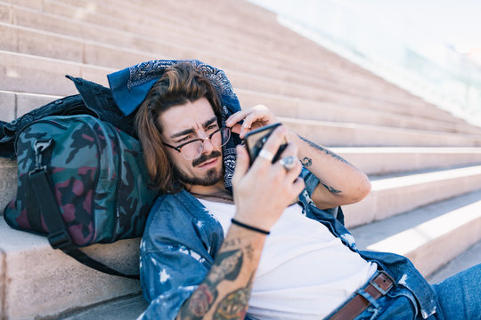 Man with long hair using phone at stairs of square.