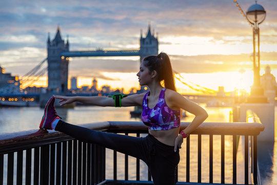 Athelitsche Frau macht ihr morgendliches Stretching bei Sonnenaufgang in der Stadt