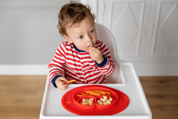 Baby in high chair eating finger food