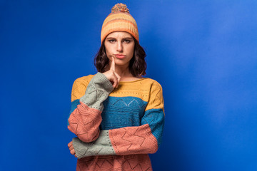 Obraz thoughtful girl in a knitted sweater and a yellow hat  - fototapety do salonu