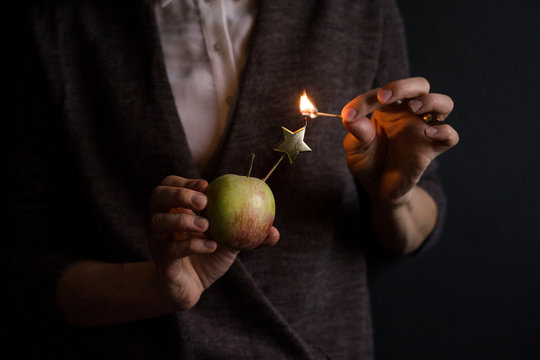 Unrecognizable person holding apple and trying to light star-shaped candle with match