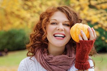 jeune et jolie femme rousse avec un potiron dans forêt nature en automne