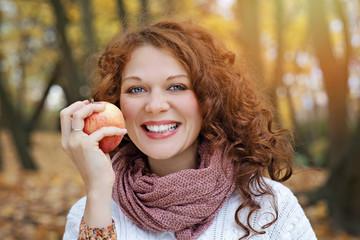 jeune et jolie femme rousse mangeant une pomme dans forêt nature en automne