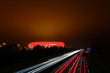 The sky above the Allianz Arena shines red from the illuminated stadium