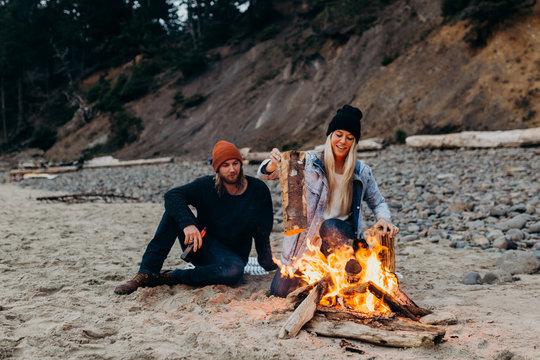 couple building a campfire on the beach