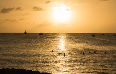 People enjoy swimming in a sea at sunset. Concept: vacation on warm sea.