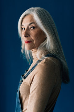 Portrait of a senior woman with grey long hair looking at camera.