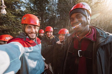 A group of friends take a selfie before starting their outdoor zip lining course