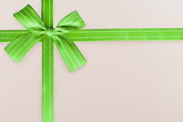 Green gift ribbon on a white textured pattern in background. Gift box wrapping concept.