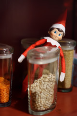 Funny Christmas toy elf on kitchen shelf