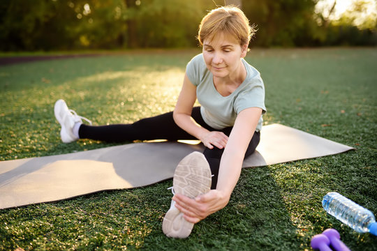 Mature woman practicing yoga outdoor exercise or doing fitness.