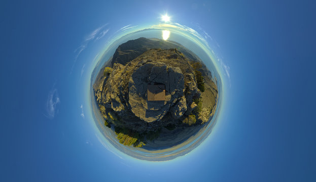 360 degree spherical tiny planet from the peak of a mountain on Antelope Island in the Great Salt Lake of Utah as the sun sets in clear skies.
