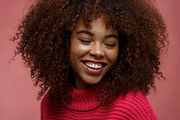 Portrait of a young African American afro woman in pink studio smiling of joy with eyes closed