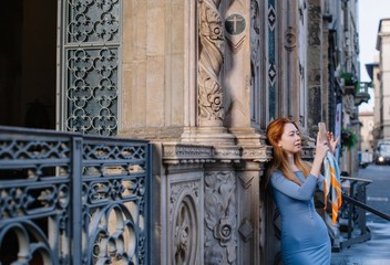 Stylish tourist girl taking picture with her smartphone in Florence