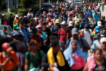 Migrants, part of a caravan traveling en route to the United States, walk by the road in Matias Romero Avendano