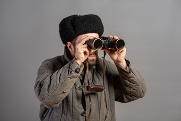 Soviet scout with a binocular keeps track of the situation, studio shot. Great Patriotic War theme