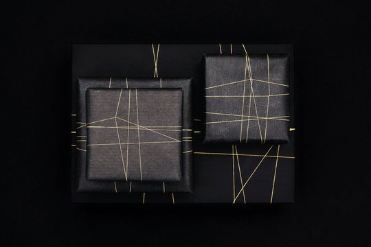 Gifts in modern black wrapping paper and a golden string