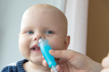 Mom cleans baby's nose using a nasal aspirator