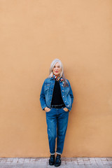 Portrait of a cool senior woman with grey long hair wearing denim clothes.